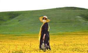一名妇女在伊朗阿尔达比勒的田野里照相。