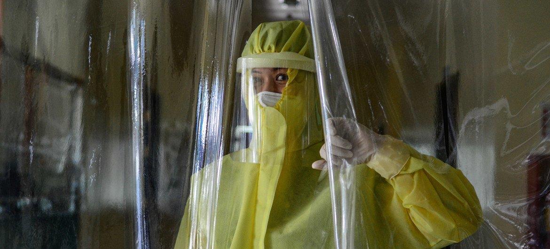 """菲律宾色阿拉,一位女医生拉起作为""""红区""""分隔的塑料布帘。"""