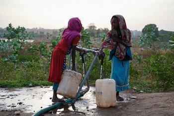 طفلتان تجمعان الماء المنقى الصالح للشرب والتي توفرها يونيسف في السودان في ولاية النيل الأزرقن والتي تضررت بشدة بسبب الفيضانات.