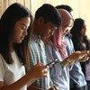 马来西亚的年轻人使用他们的手机保持联系。