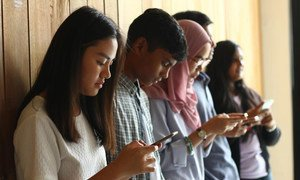 Young people in Malaysia use their cell phones to stay connected.