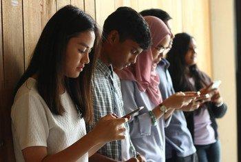 Jovens na Malásia usando seus celulares