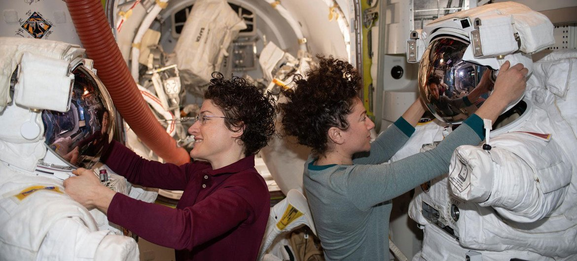 NASA astronauts Christina Koch (left) and Jessica Meir work on their spacesuits ahead of a spacewalk they are conducting.