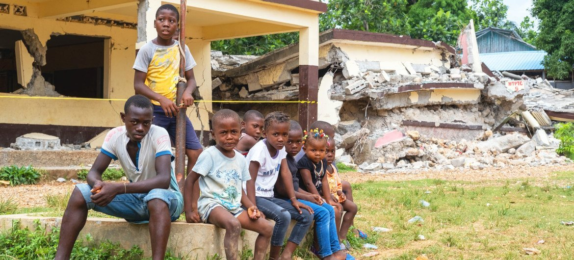 Children sit in front of their school, Notre Dame du Perpétuel Secours de Latibolière, destroyed during the 14th August earthquake in Haiti.