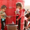 Two young children wait to collect water trucked in by UNICEF from other areas of the Middle East to Tal Tamer, Syria. (16 October 2019)