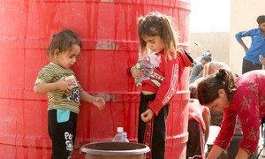 Deux enfants attendent de collecter de l'eau apportée par l'UNICEF à Tall Tamr, dans le nord-est de la Syrie.