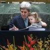 Бывший государственный секретарь США Джон Керри с внучкой на руках подписывает Парижское соглашение. Апрель 2016 года