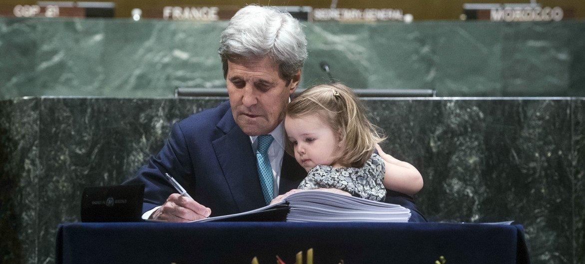 El entonces Secretario de Estado de Estados Unidos, John Kerry, junto a su nieta, firman el Acuerdo de París.