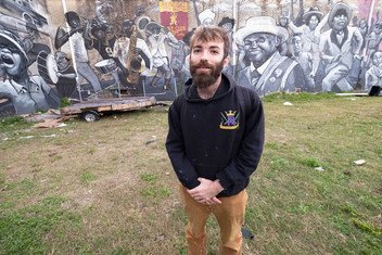 Henry Lipkis in front of his monumental mural depicting a traditional parade in New Orleans.