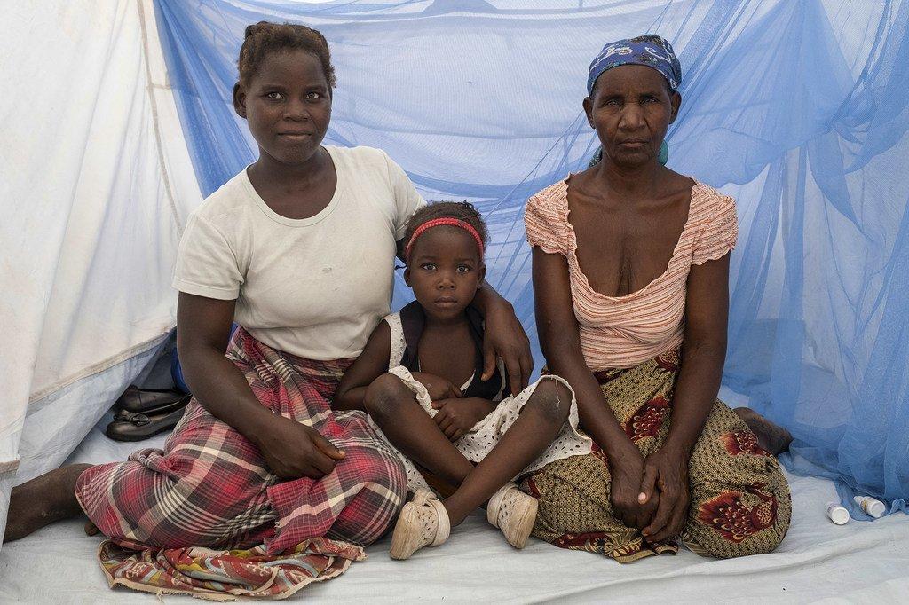Au Mozambique, trois générations d'une famille assises ensemble sur un lit protégé par une moustiquaire imprégnée.