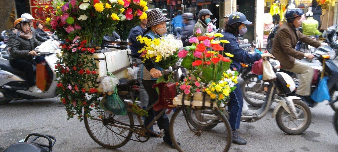 वियतनाम के पर्यटन प्रसिद्ध स्थान हनोई में फूल बेचती हुई एक महिला, मगर वायु प्रदूषण से बचने के लिए उसे मास्क पहनना पड़ रहा है.