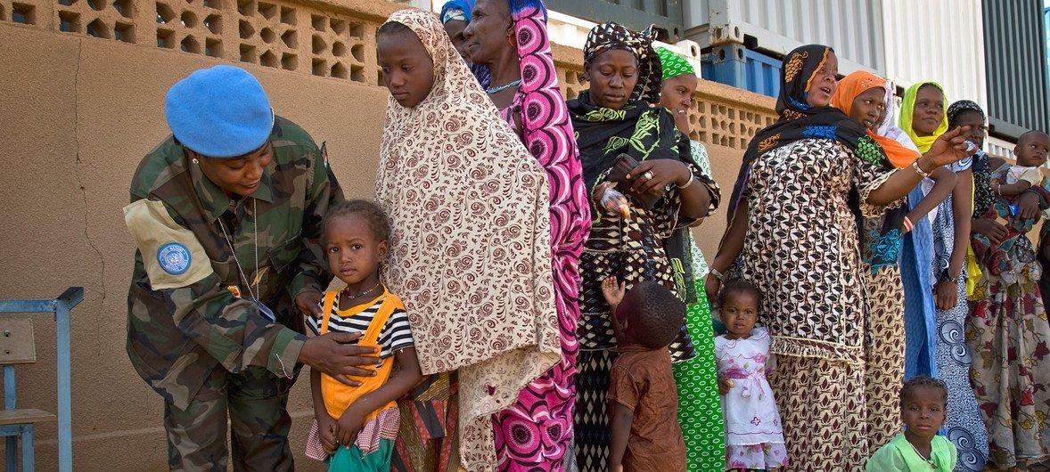 Des Maliens attendent de recevoir une consultation médicale dans une clinique gérée par des Casques bleus du Niger à Gao, au Mali.