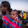 A refugee from Tigray waits in line with her baby to receive food in the Um Rakuba refugee settlement in Sudan.