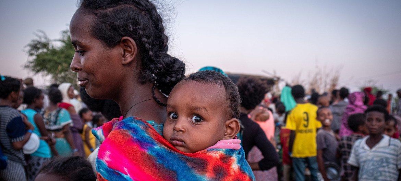 لاجئة من تيغراي تنتظر في صف مع طفلها لتلقي الطعام في مخيم أم راكوبة للاجئين في السودان.