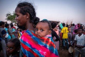 Une réfugiée du Tigré fait la queue avec son bébé pour recevoir de la nourriture dans le camp de réfugiés d'Um Rakuba au Soudan.