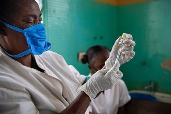 A health worker at a local health centre in Kinshasa, Democratic Republic of the Congo, prepares a vaccine injection.
