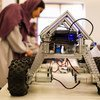 A girl in Afghanistan shows a robot she has built at an exhibition in Kabul.