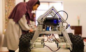 شابة أفغانية تشارك في معرض في العاصمة كابول، وبجوارها روبوت قامت بصنعه.