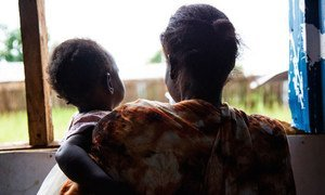 Woman holds her youngest daughter at the Wisdom Center in Juba's Gurei area in South Sudan after being beaten by her husband.