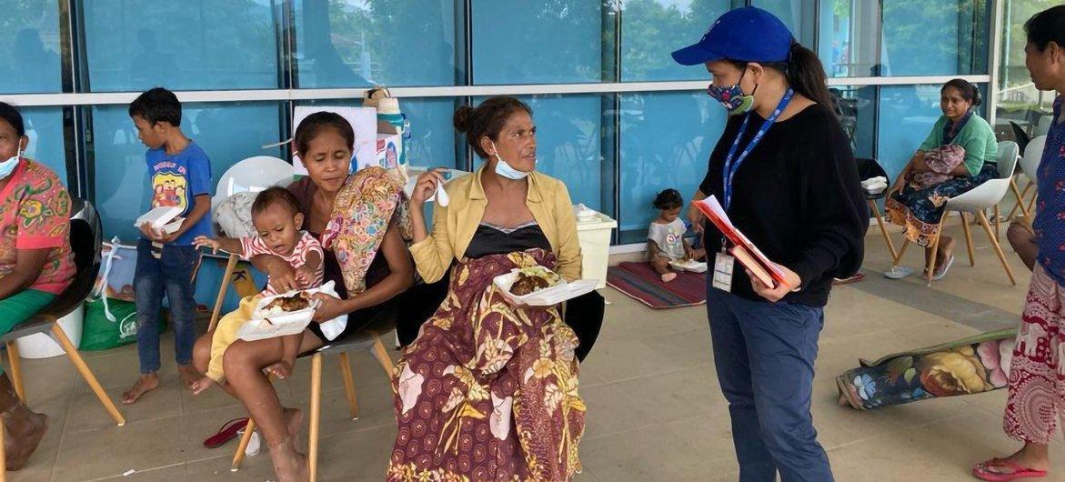 Funcionária da OIM fala com pessoas afetadas pelas enchentes em Timor-Leste