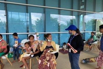 Funcionária da OIM, uma das agências da ONU que participa do apelo, fala com pessoas afetadas pelas enchentes em Timor-Leste