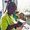 Un empleada de Clean the World recogiendo las barras recicladas de jabón que salen de una cinta transportadora.