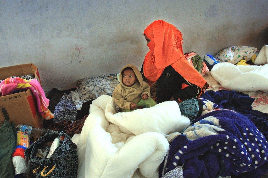 سيّدة صومالية تجلس مع رضيعها ابن العام في مركز قندوفة للاحتجاز قرب بنغازي بعد أن فرّت بسبب العنف في بلدها ودخلت بطريقة غير قانونية إلى ليبيا.