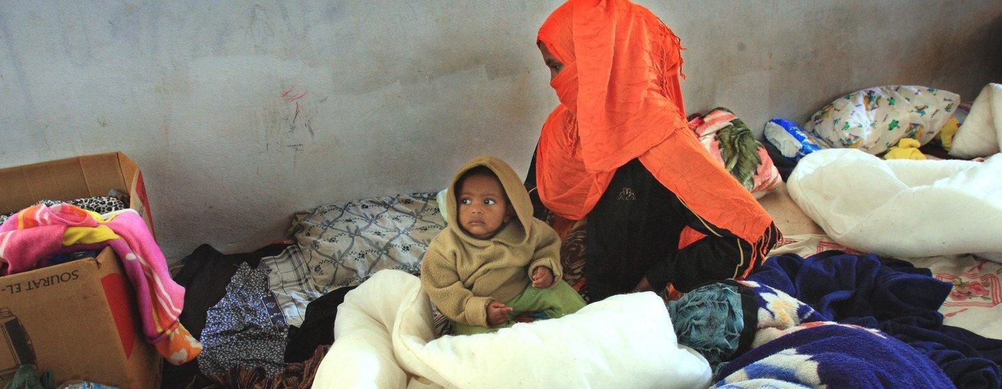 Une femme somalienne est assise avec son enfant d'un an, dans le centre de détention de Ganfoda, près de Benghazi, après avoir fui les violences dans son pays et pénétré illégalement en Libye.