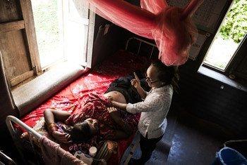 Une sage-femme effectue un examen prénatal pour une future mère dans un poste de santé du Népal rural.
