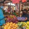 一名男子在肯尼亚的一个绿色市场上购买新鲜农产品。