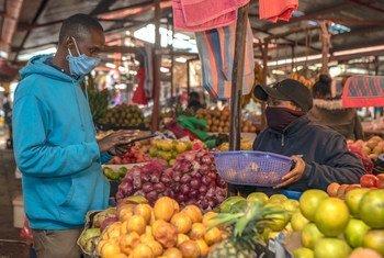 A man buys fresh produce at a green market in Kenya.
