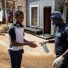 Mjini Johannesburg Afrika Kusini, mkazi wa makazi yasiyo rasmi ya Setswetla akipuliziwa vitakasa mikono.