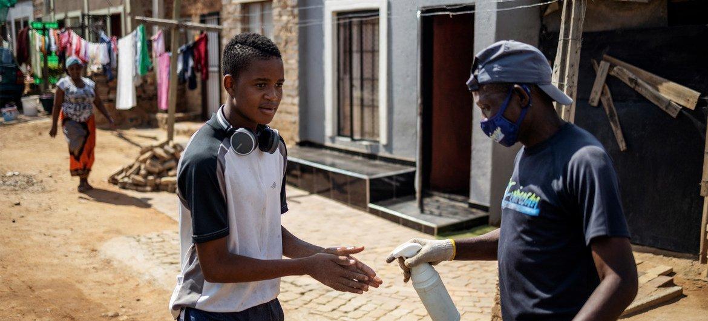 Em Joanesburgo, na África do Sul, homens desinfetam mãos como medida de combate à Covid-19