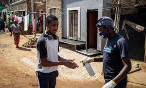 Le 23 avril 2020 à Johannesburg, en Afrique du Sud, un habitant du quartier informel de Setswetla se fait asperger les mains de désinfectant pour les mains.