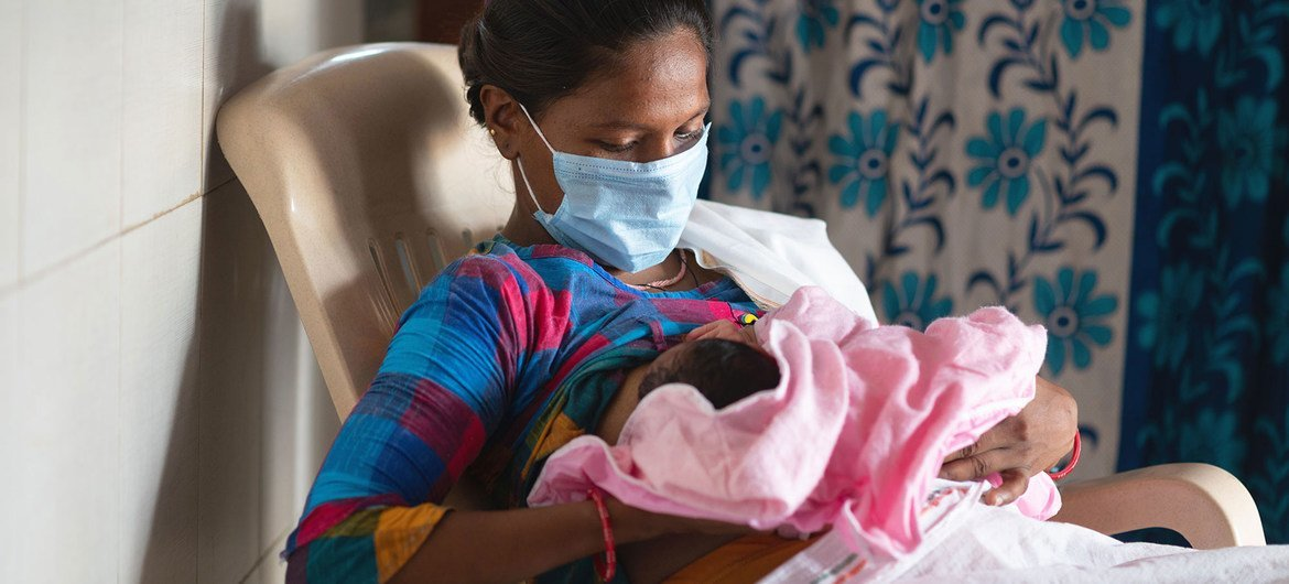 A woman breastfeeds her baby in a labour room in India shortly after giving birth.