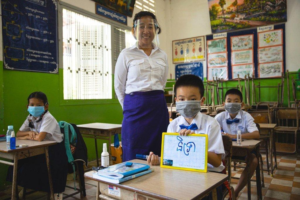 Dans une salle de classe de Phnom-Penh, la capitale du Cambodge, une enseignante et ses élèves portent des masques en raison de la pandémie de Covid-19