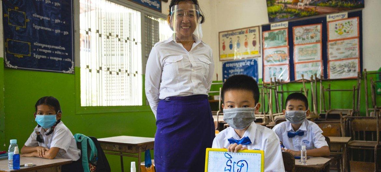 Una maestra y sus alumnos practican medidas de seguridad COVID en una escuela de Camboya.