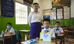 A teacher and her students practice COVID-19 school re-opening guidelines by wearing face masks and maintaining physical distance at a primary school in Phnom Penh, Cambodia.