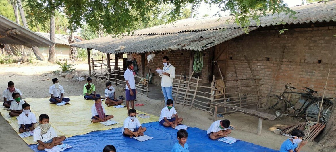 Children in Odisha, India take lessons in the open air as a precaution against COVID-19.