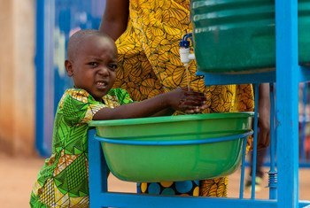 A young Burundian refugee washes his hands before boarding a bus with his family to voluntarily return home after living in exile since 2015.