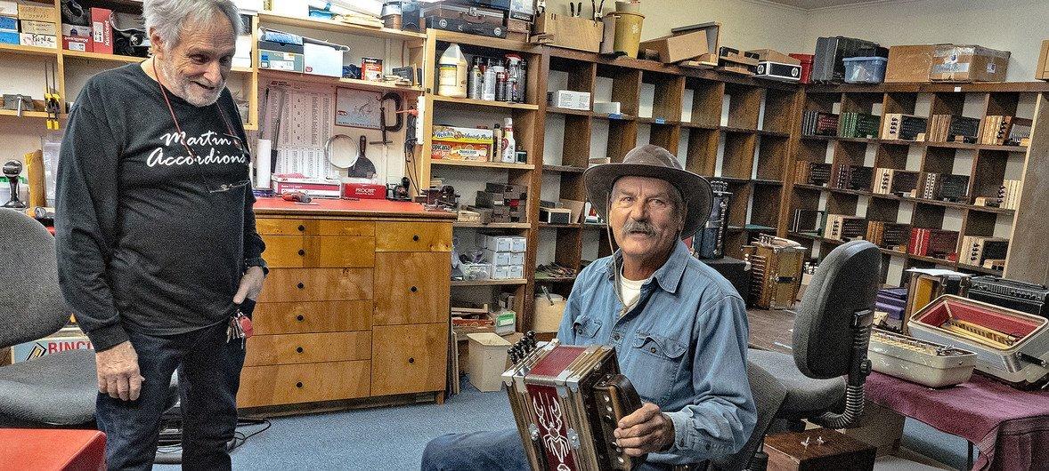 Clarence Martin (à gauche) parle à un client dont il a réparé l'accordéon.