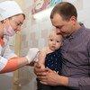 Un bébé dans les bras de son père tandis qu'une infirmière administre sa première dose de vaccin contre la rougeole, les oreillons et la rubéole.