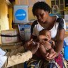 A mother holds her 3-month-old baby as he receives a vaccination against measles at a health centre in Lubumbashi, Democratic Republic of the Congo.