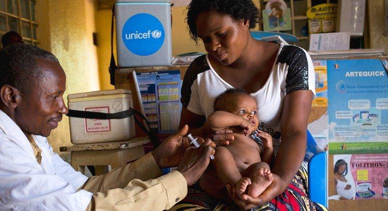 Una madre sujeta a su hijo mientras recibe una vacuna contra el sarampión.