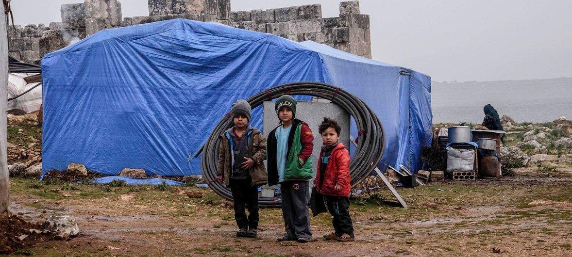 أطفال يقفون أمام خيمة في مخيم للنازحين في إدلب شمالي سوريا