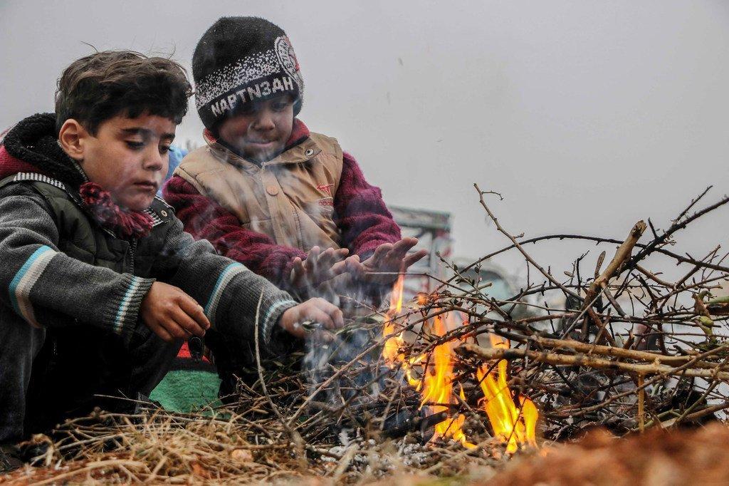 أطفال يلهون أمام مخيم للنازحين في جنوب إدلب، بسوريا