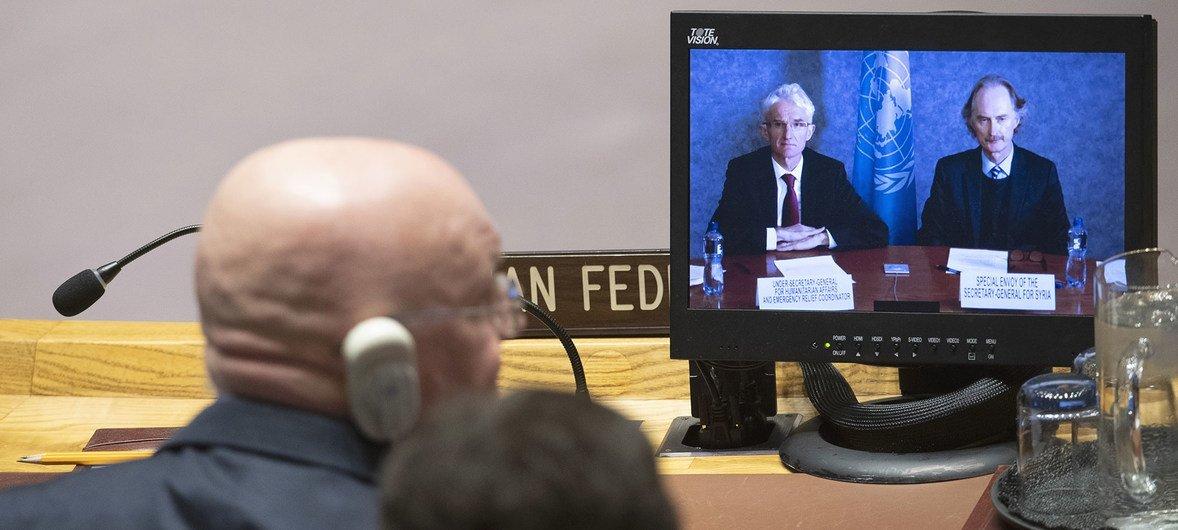 संयुक्त राष्ट्र के मानवीय सहायता कार्यों के प्रमुख मार्क लोकॉक (स्कीन पर बाएँ) और सीरिया के लिए संयुक्त राष्ट्र के विशेष दूत गियर पीडरसैन (स्क्रीन पर दाएँ) सुरक्षा परिषद को इदलिब की स्थिति के बारे में जानकारी देते हुए.