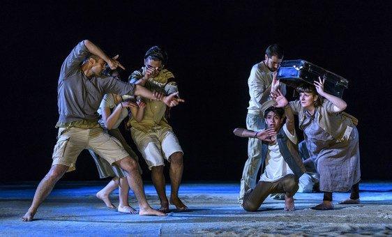 """Refugiados, migrantes y adolescentes griegos actúan en la obra """"El viaje"""", presentada en el Teatro Nacional de Grecia. La foto es parte de la exposición """"Migrantes en las ciudades"""", auspiciada por ONU Hábitat y UNICEF."""