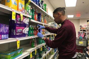 Un empleado de una farmacia de Nueva York lleva guantes para protegerse del coronavirus mientras repone los jabones en una estantería
