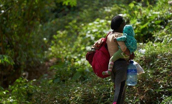 Mãe e filho chegam a acampamento para migrantes em Darien, Panamá.